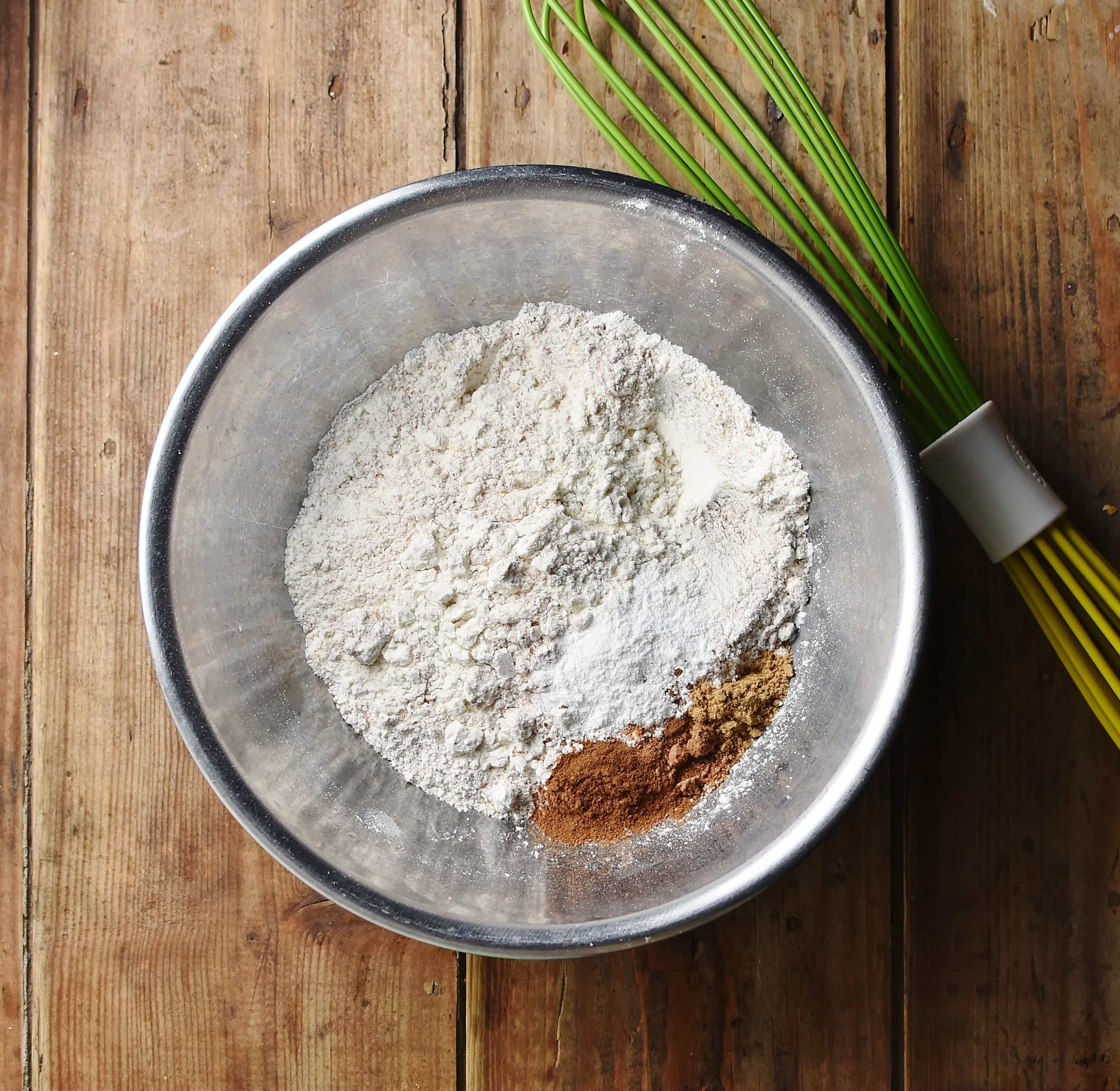 Flour and spices in metal bowl with green whisk in background.
