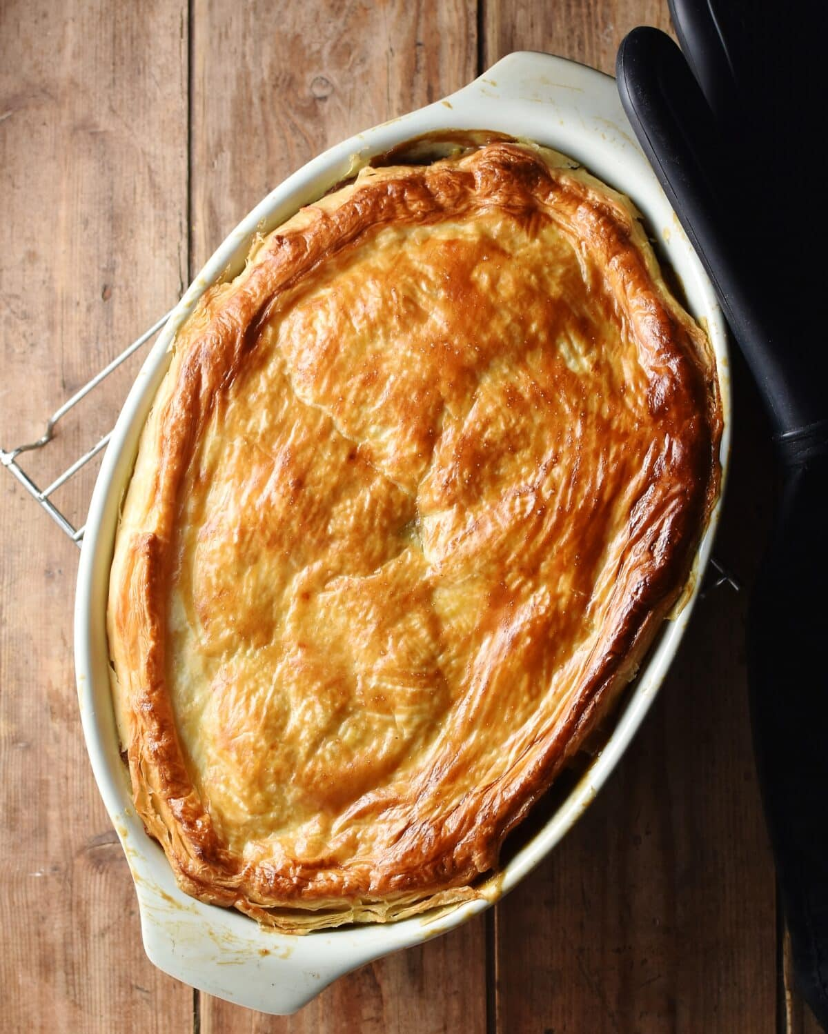 Pie with golden brown pastry on top in oval dish.