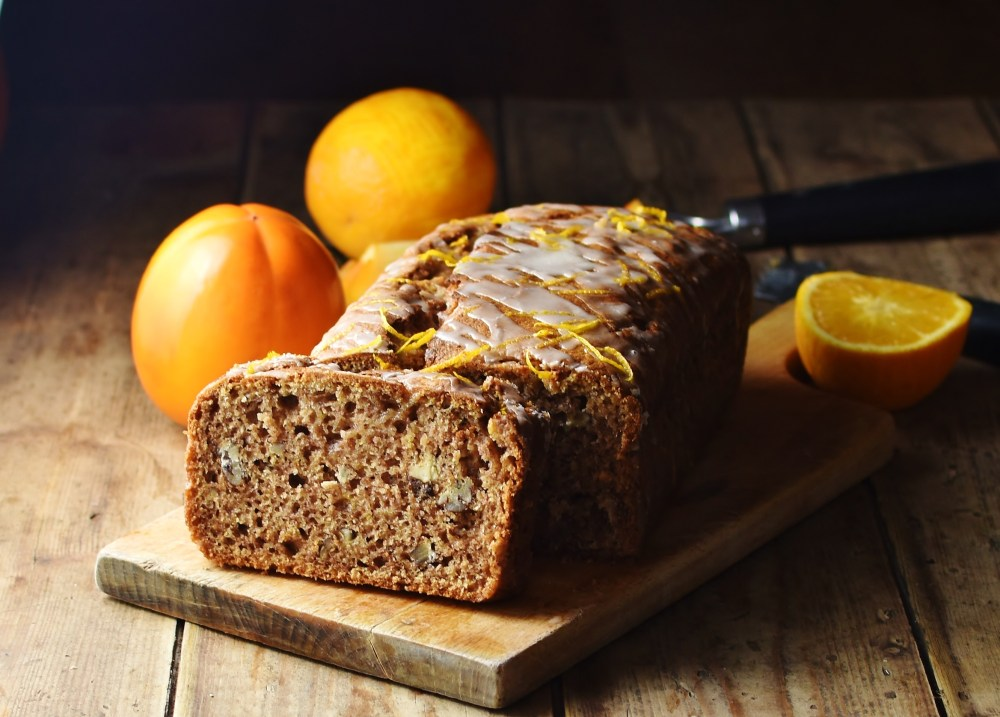 Side view of persimmon loaf on top of wooden board with persimmon and orange in background.