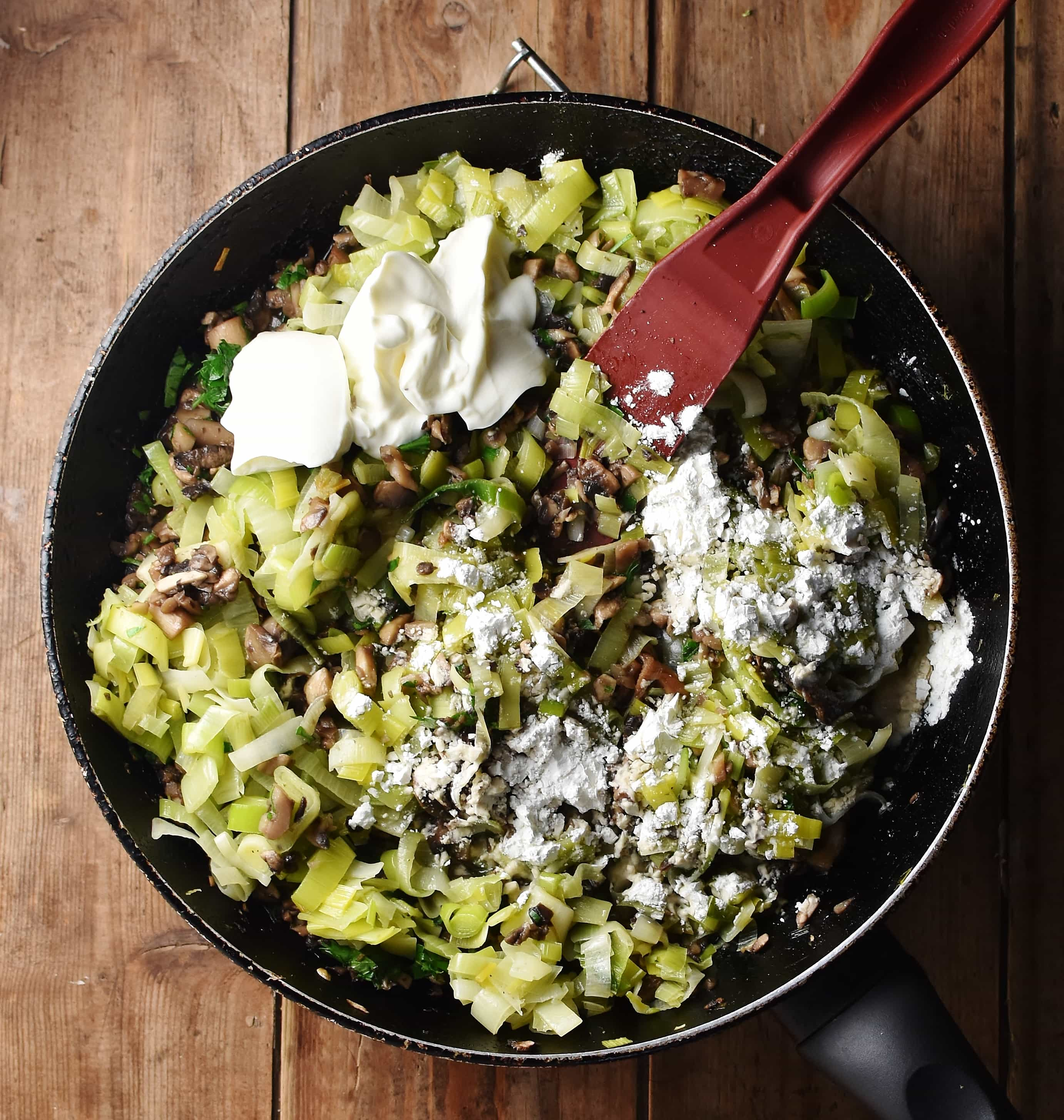 Chopped leeks, mushrooms, yogurt and flour in large skillet with red spatula.