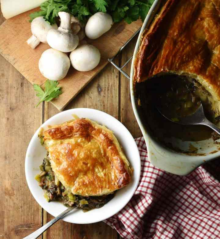 Top down view of mushroom and leek pie with golden brown pastry in small white bowl with for, checked reed-and-white cloth, pie in oval dish and mushrooms on wooden board in background.