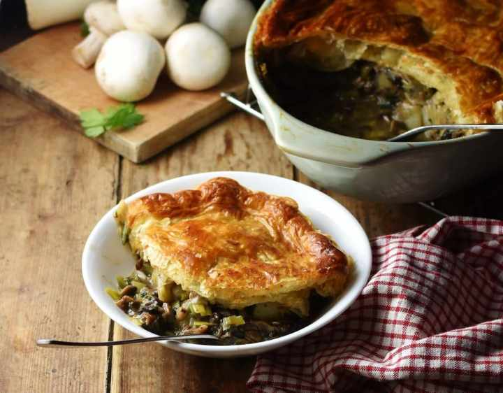 Side view of leek and mushroom pie topped with golden brown pastry on white bowl with fork, plaid red-and-white cloth to the right, pie in dish and mushrooms in background.