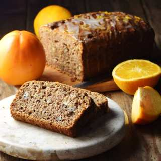 2 slices of persimmon bread on marble tray, with persimmon, orange and bread loaf in background.