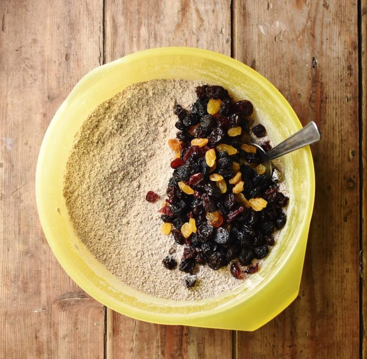 Flour mixture and dried fruit in large yellow bowl with spoon.