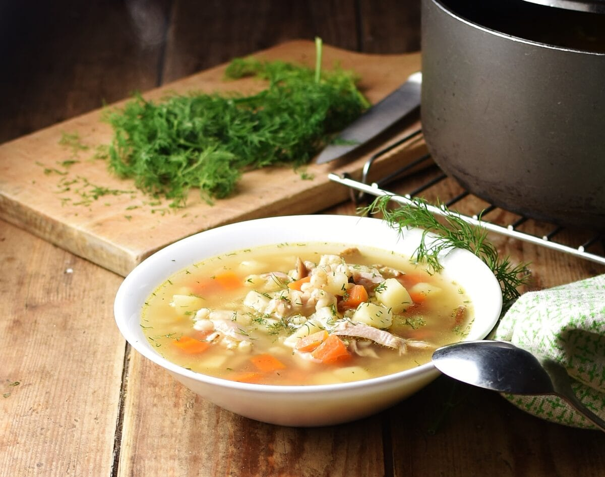 Side view of chunky barley soup in white bowl with spoon, fresh dill on wooden board and black pot in background.
