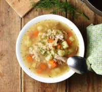 Chunky potato, carrot and barley soup in white bowl with spoon, green cloth to the right and dill at the top.
