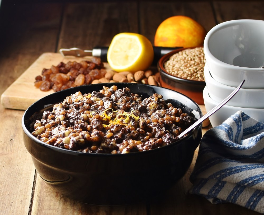 Wheat berries, nuts and raisins mixture with spoon in black bowl, with raisins, nuts, fruit and white bowls stacked in background.
