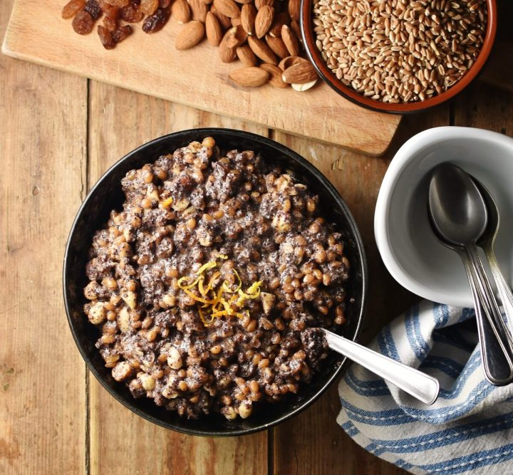 Fruit, wheat and nut kutia mixture in black bowl with spoon, blue-and-white stripy cloth to the right, white dish with spoons and grains and nuts in background.
