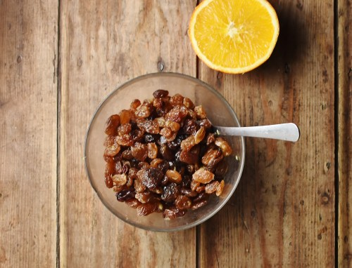 Raisins in bowl with spoon and orange half in background.