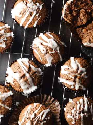 Top down view of gingerbread muffins with icing on top of rack and tray.