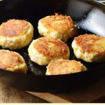 Potato turkey patties in frying pan, with patties on white plate in background.