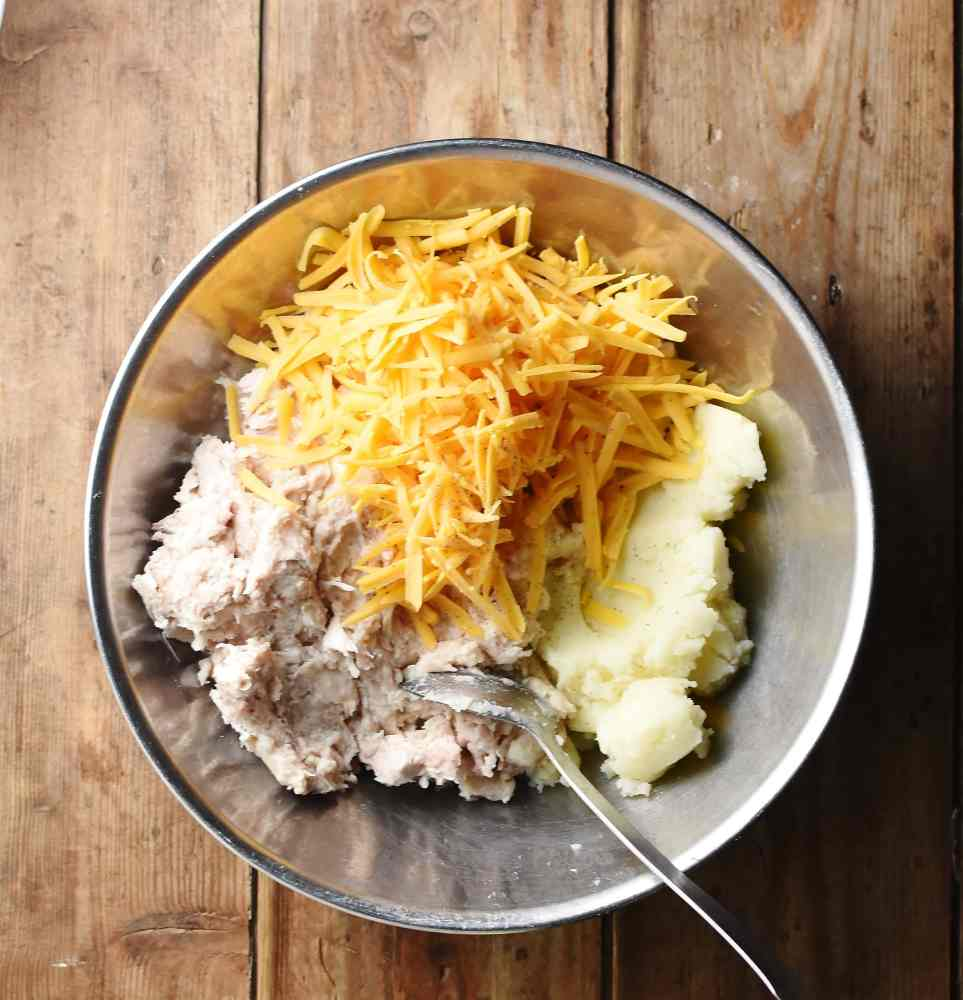 Turkey mixture, mashed potato and grated cheese in large metal bowl with spoon.