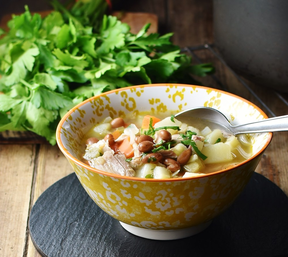 Side view of turkey soup with chunky vegetables in yellow bowl with spoon and parsley bunch in background.