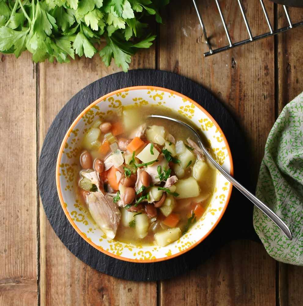 Chunky soup with turkey and vegetables in yellow bowl with spoon, green cloth to the right and parsley at the top.