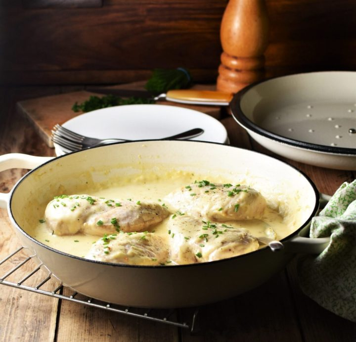 Side view of chicken in white sauce in large shallow white pan, with plates, lid and pepper grinder in background.