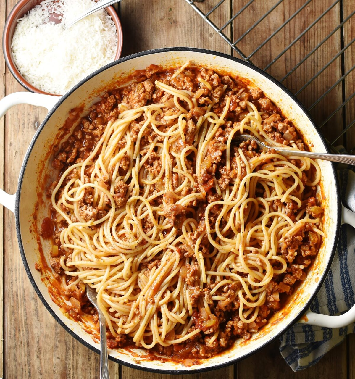 Spaghetti bolognese in large white shallow dish with grated cheese in small dish and rack at the top