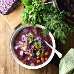 Chunky red cabbage vegetable soup in white bowl with spoon, dill, parsley, green cloth and red cabbage in background.