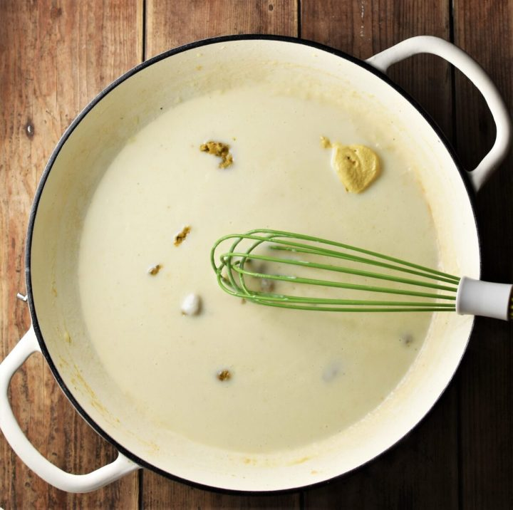 Milk, crumbled stock cube and mustard in large shallow white pan with green whisk.