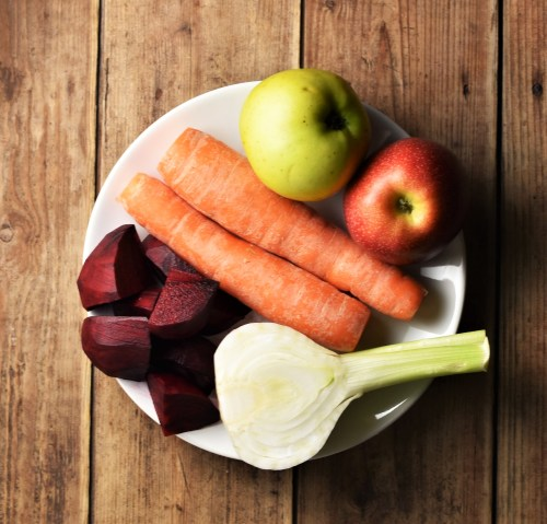 2 carrots, 2 apples, halved fennel and chopped beet on white plate.