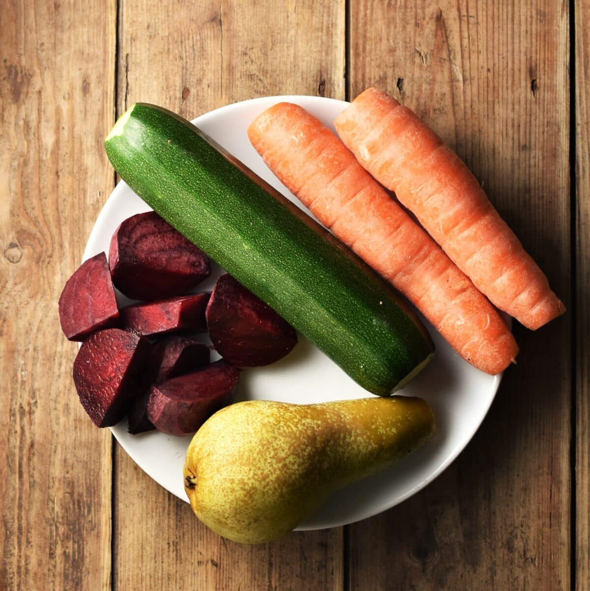 Chopped beet, zucchini, 2 carrots and pear on white plate.