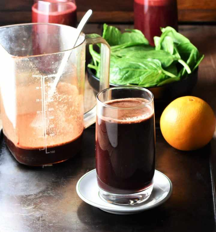 Side view of beet spinach juice in glass on top of white saucer, with orange, spinach and juice in measuring container with spoon in background.