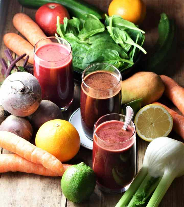 Beetroot juice in 3 glasses, with fresh fruit and vegetables in background.