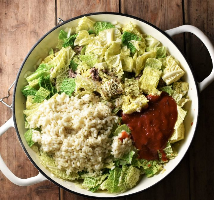 Chopped cabbage, rice and tomato passata in large shallow white pan.
