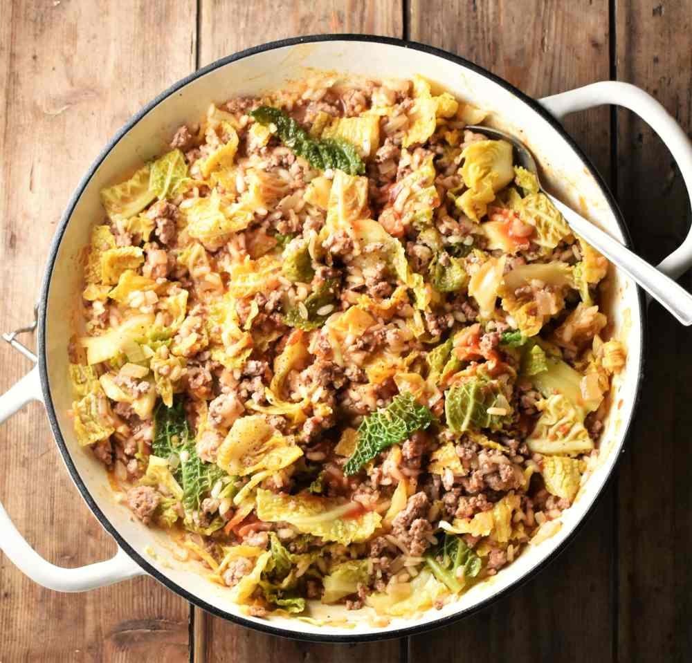 Chopped cabbage, ground meat and rice in large, shallow, white dish with spoon.