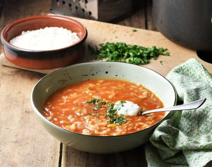 Side view of tomato soup with rice in green bowl with spoon, rice in brown dish, chopped herbs and green cloth in background.
