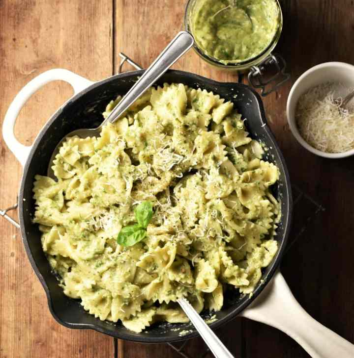 Top down view of avocado pesto pasta in skillet with 2 spoons, pesto and grated cheese in background.