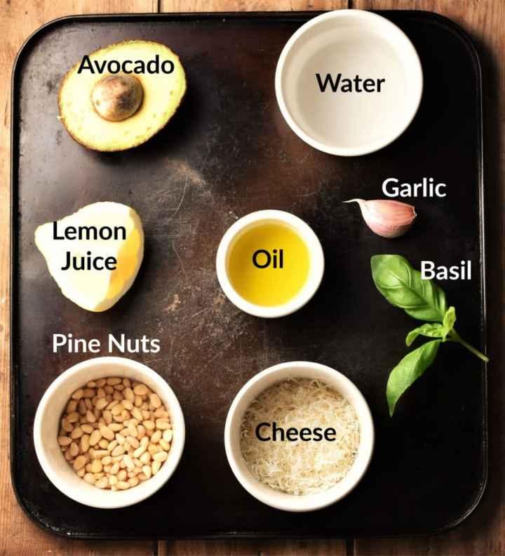 Avocado pesto sauce ingredients in individual dishes.