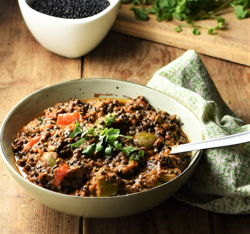 Side view of black lentils stew in green bowl with spoon and lentil in white bowl in background.