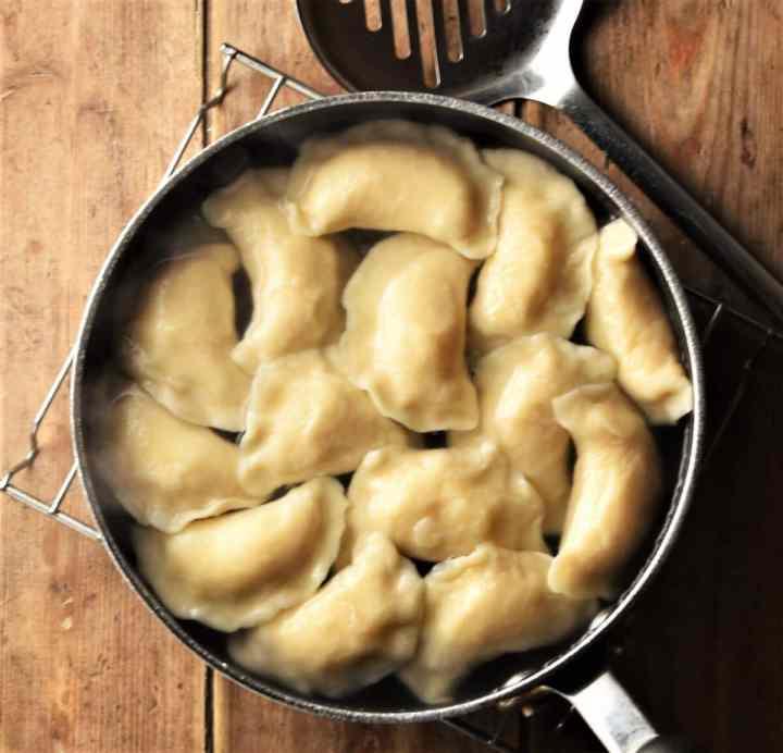 Boiling perogies in pot.
