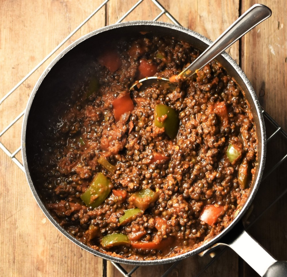 Lentil stew with vegetables in pot with spoon.