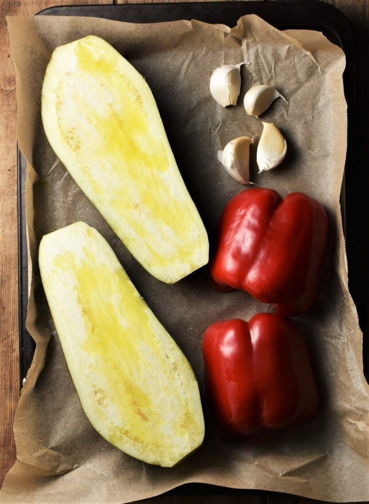Halved eggplant, red pepper and 4 garlic cloves on top of parchment.