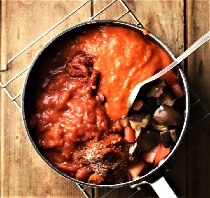 Chopped eggplant, tomatoes and pepper puree in pot with spoon.