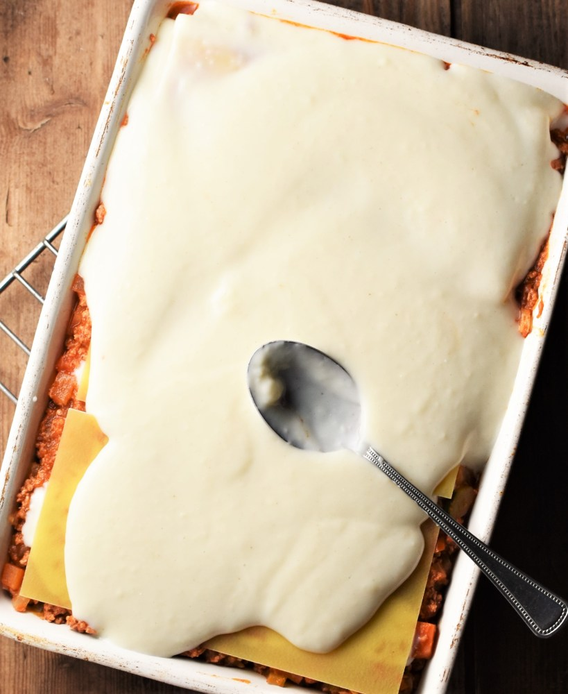 Lasagna partly covered with white sauce with spoon.