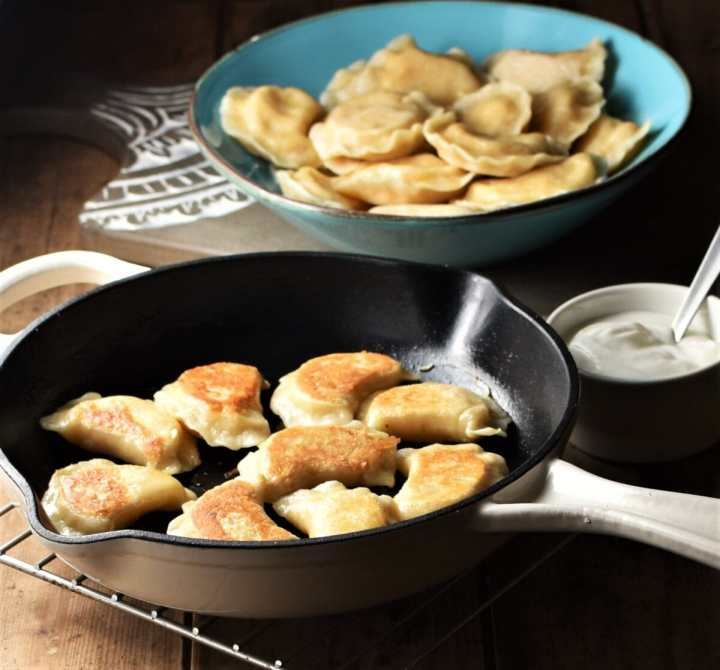 Side view of fried pierogies in pan, with perogies in blue bowl and sour cream in background.