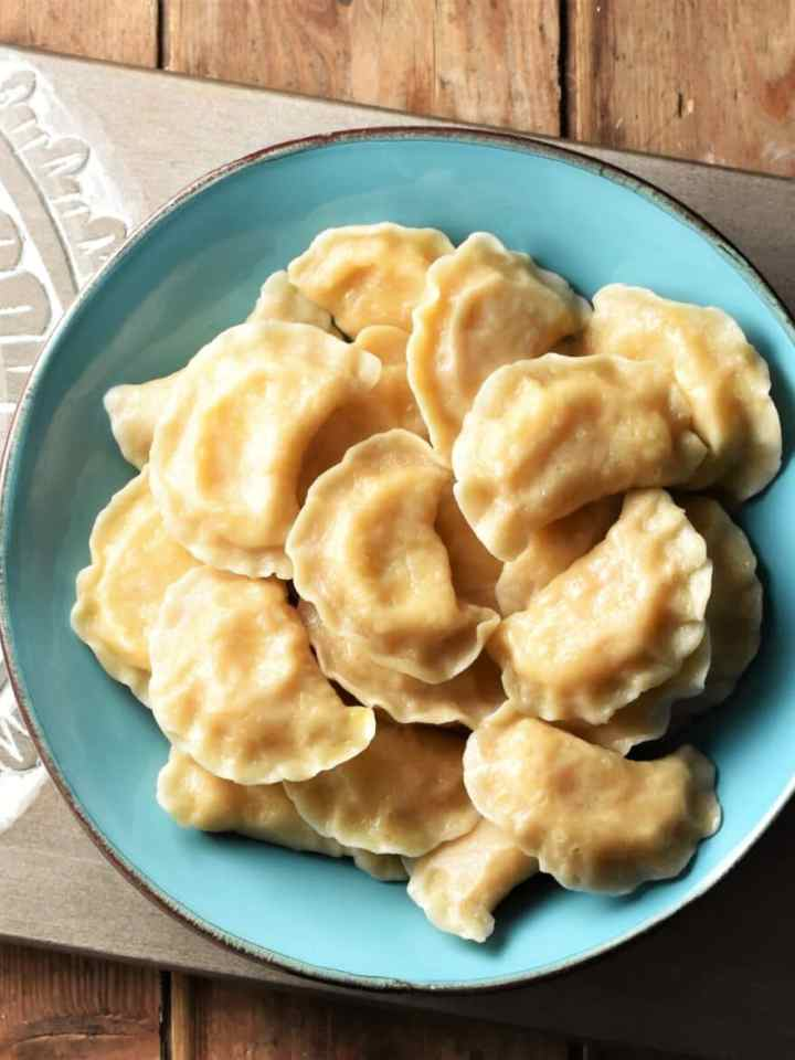 Top down view of homemade perogies in blue bowl.