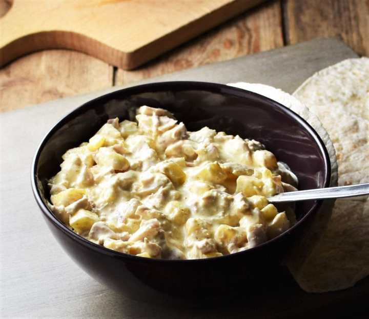 Side view of creamy pineapple chicken salad in bowl with spoon and wraps to the right.
