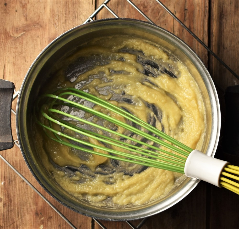 Roux in saucepan with green whisk.