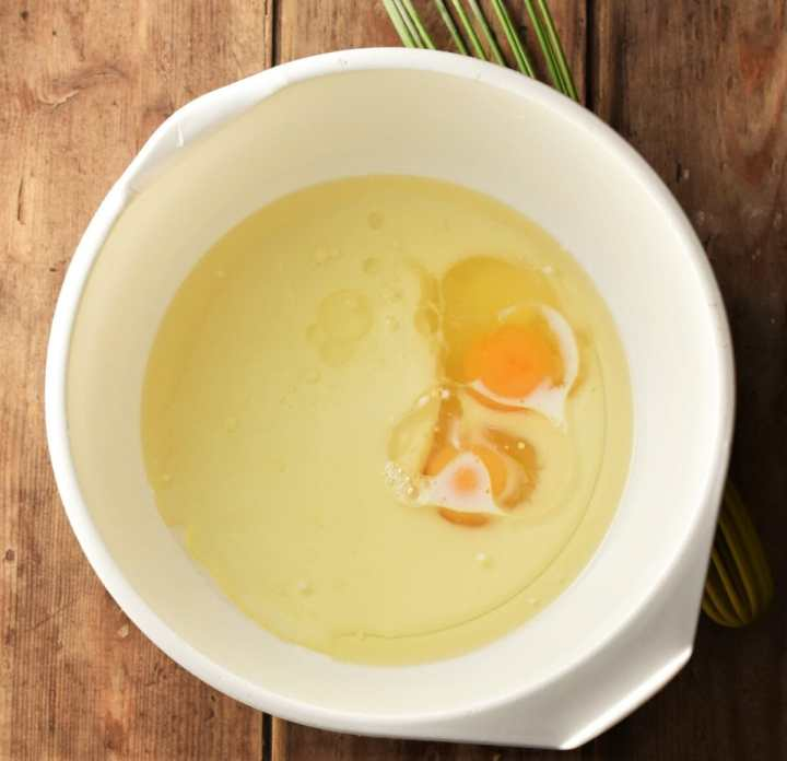 Milk, oil and 2 eggs in large white bowl.