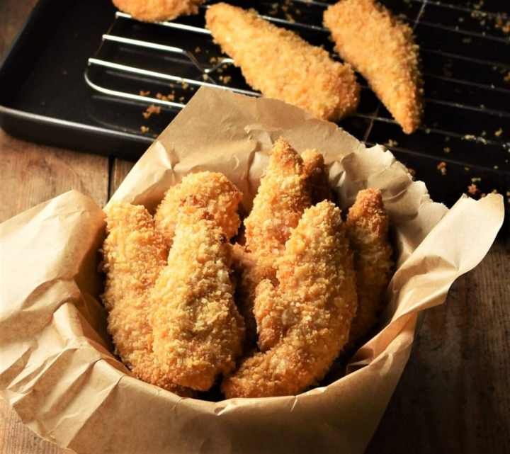 Side view of crispy chicken fingers in bowl lined with parchment.