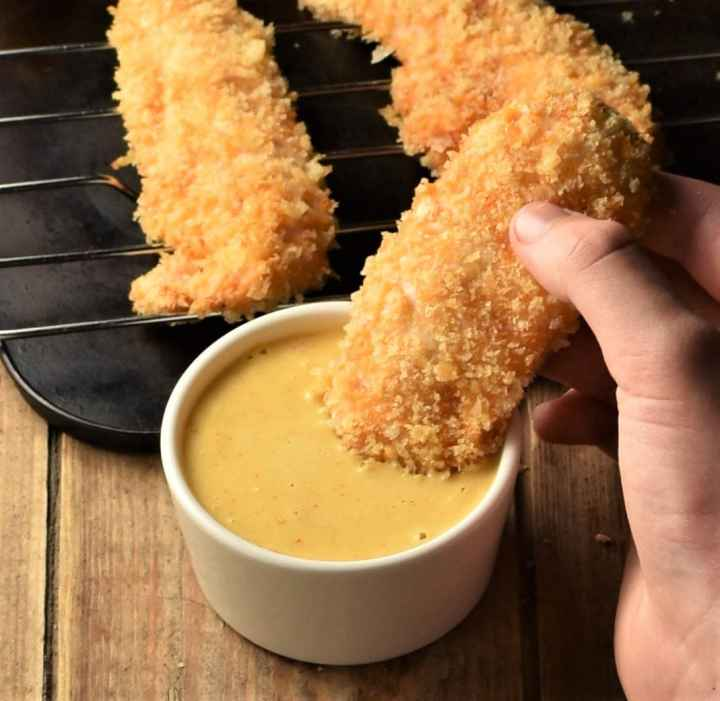 Chicken tender dipped in yellow sauce with baked tenders in background.