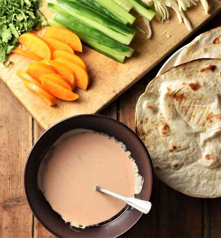 Creamy sauce, tortillas and chopped fruit and begetables on top of wooden board.