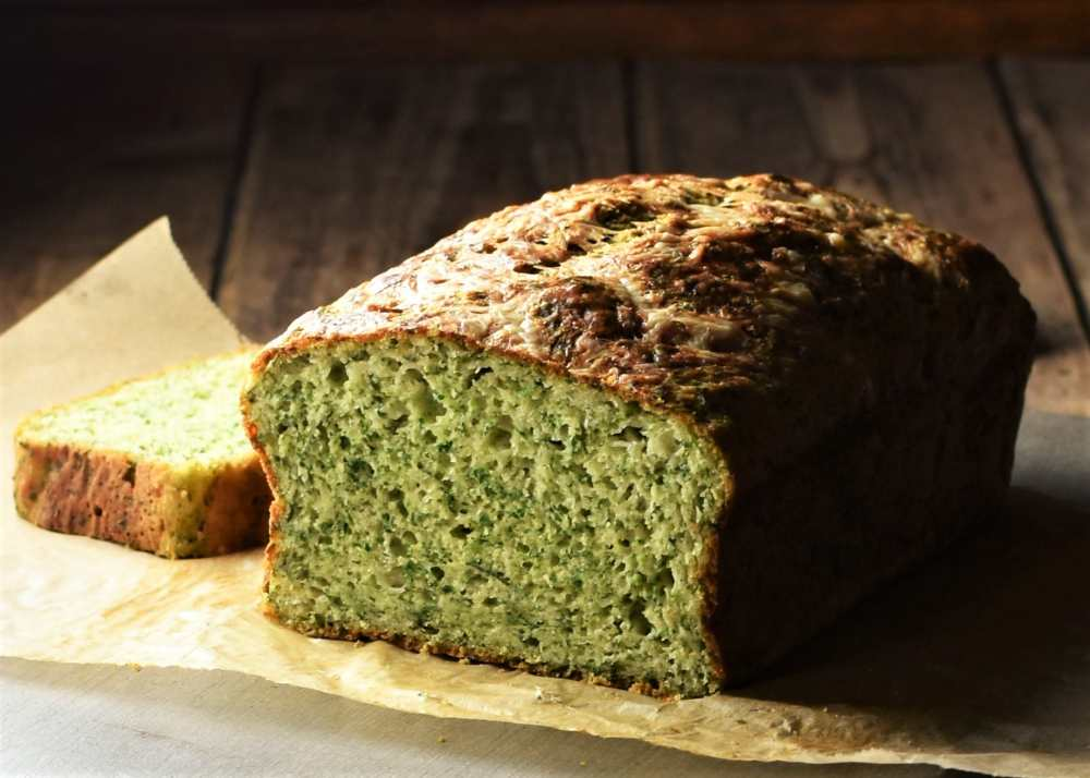 Side view of spinach bread with slice behind on top of parchment.
