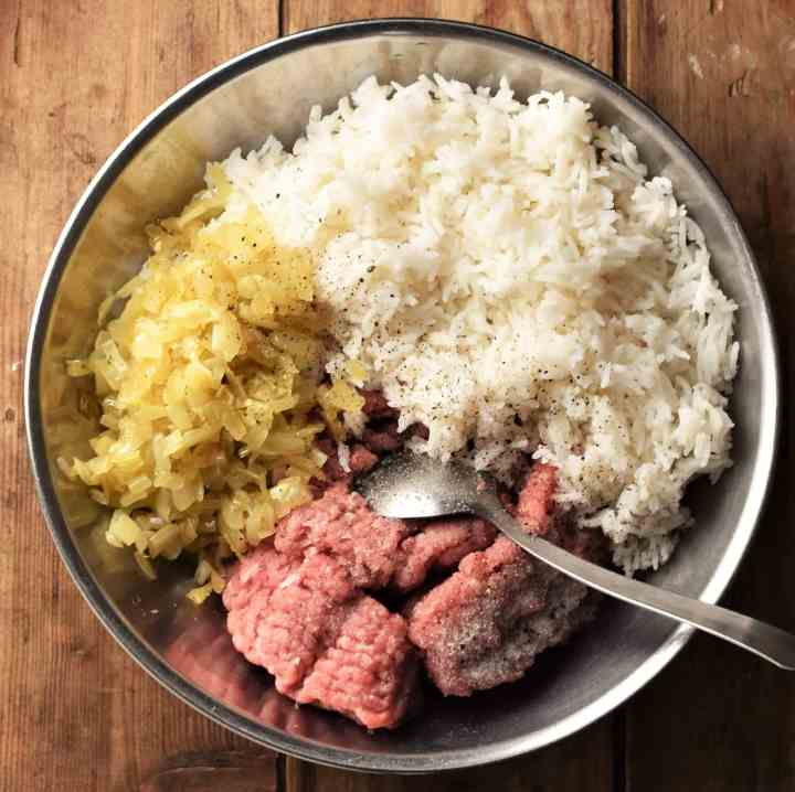 Meat, fired onion and cooked rice in metal bowl with spoon.