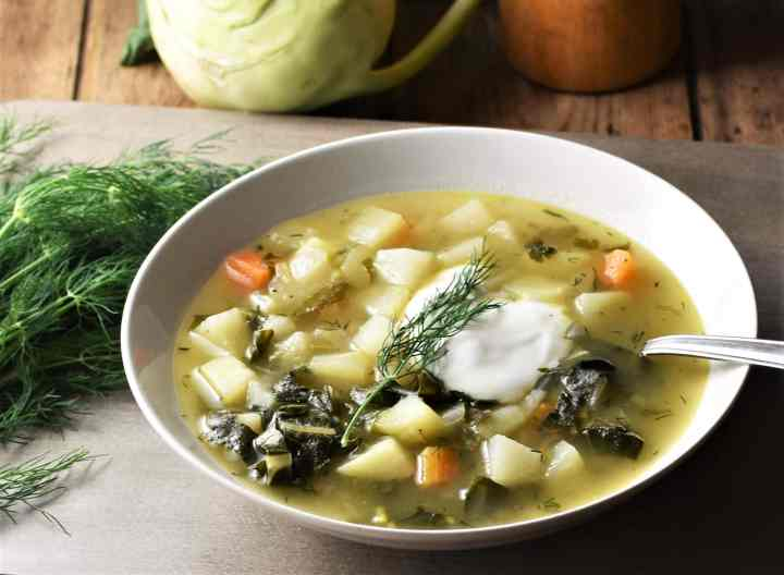 Side view of chunky vegetable soup with yogurt in white bowl with spoon.