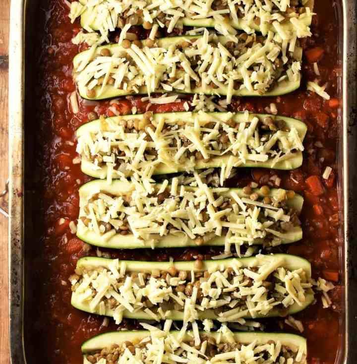 Unbaked stuffed zucchini in tomato sauce.
