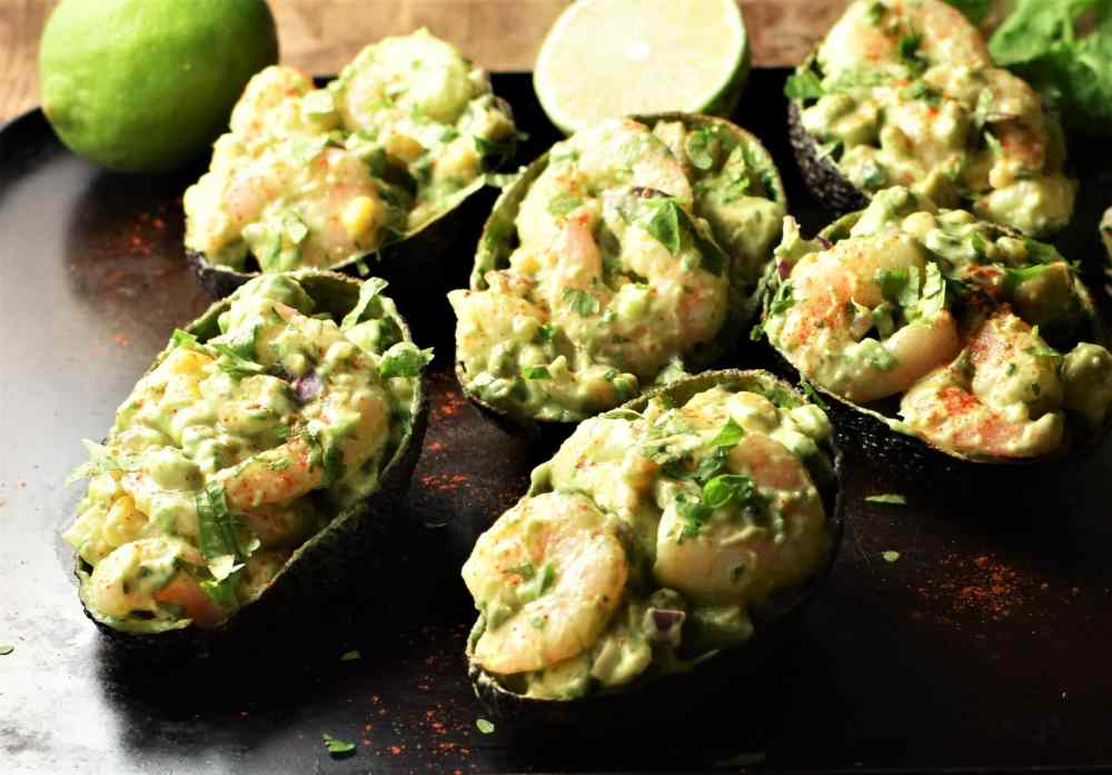 Shrimp stuffed avocado halves with limes in background.